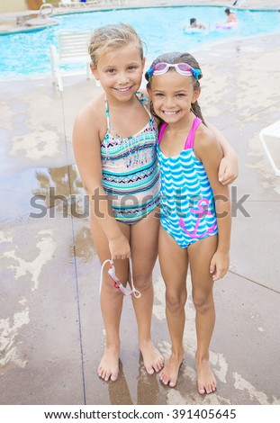 Two cute little girls playing together in their back yard swimming pool on a warm summer day - stock photo