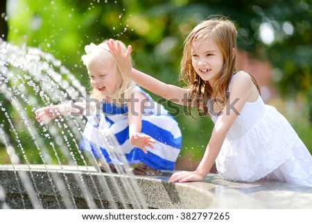 Two cute little girls playing with a city fountain on hot and sunny summer day - stock photo