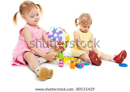 Two cute little girls playing with colorful blocks