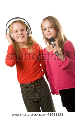 Two cute little girls with headphones and microphone isolated - stock photo