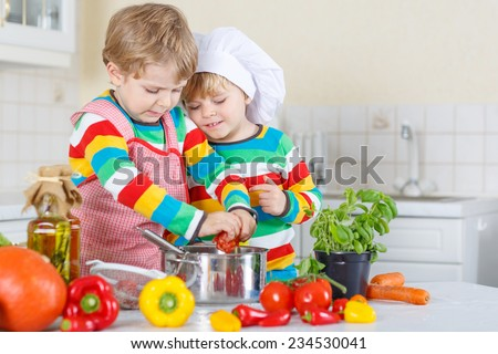 Two cute little kid boys cooking italian soup and meal with fresh vegetables in home's white kitchen. Sibling children in colorful shirts. - stock photo
