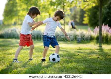 Two cute little kids, playing football together, summertime. Children playing soccer outdoor