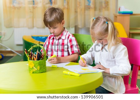 Two cute little preschool kids drawing with crayons at the table - stock photo