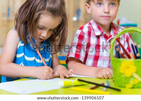 Two cute little prescool kids drawing with crayons at the table