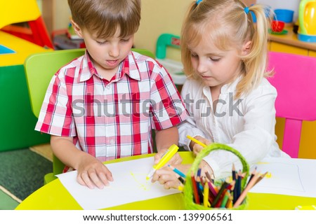 Two cute little preshcool kids drawing with crayons at the table - stock photo