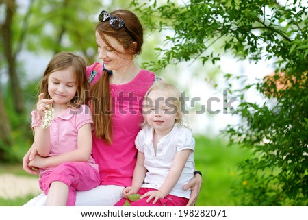 Two cute little sisters and their mother outdoors - stock photo