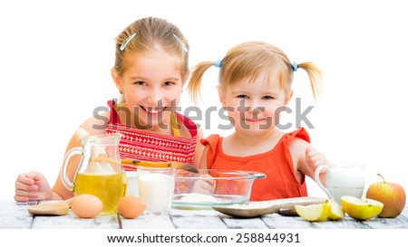 two cute little sisters cooking and looking into the camera on a white background - stock photo