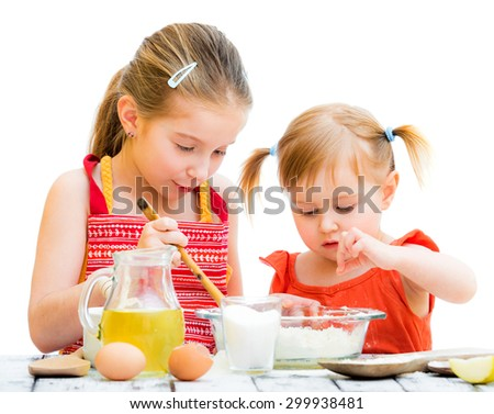 two cute little sisters cooking, on a white background - stock photo