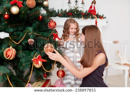 Two cute little sisters decorate a Christmas tree. Christmas mood - stock photo