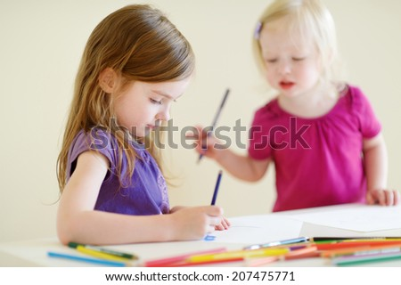 Two cute little sisters drawing with colorful pencils at a daycare - stock photo