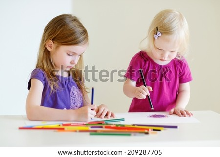 Two cute little sisters drawing with colorful pencils at a daycare