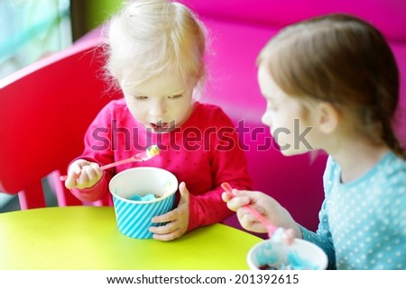Two cute little sisters eating ice cream together in a colorful outdoor cafe - stock photo