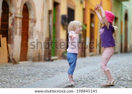 Two cute little sisters having fun outdoors - stock photo