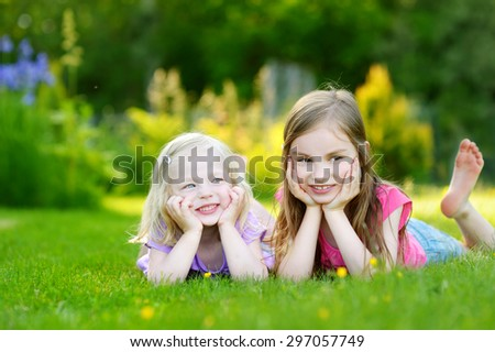 Two cute little sisters having fun while laying on the grass on a sunny summer day - stock photo