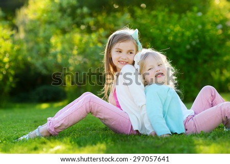 Two cute little sisters having fun while sitting on the grass on a sunny summer day - stock photo