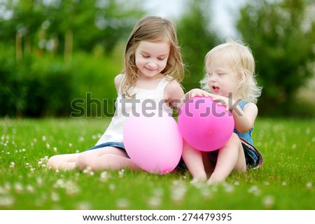 Two cute little sisters having fun with pink balloons while sitting on the grass on a sunny summer day - stock photo