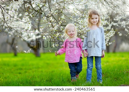 Two cute little sisters in blooming cherry garden on beautiful spring day - stock photo