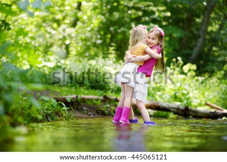 Two cute little sisters playing in a river wearing raining boots on warm and sunny summer day