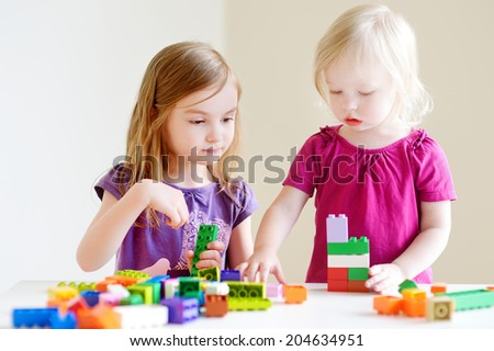 Two cute little sisters playing with colorful plastic blocks at home - stock photo