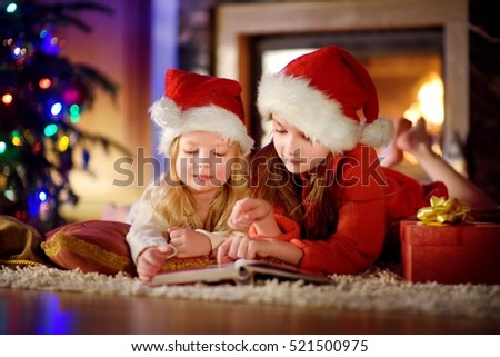 Two cute little sisters reading a story book together under a Christmas tree on Christmas eve at home