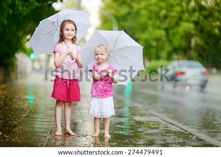Two cute little sisters standing in a puddle holding umbrella on a rainy summer day - stock photo