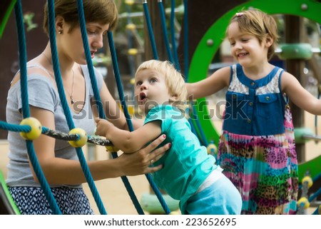 Two cute little sisters with mother at action-oriented playground in summer park - stock photo