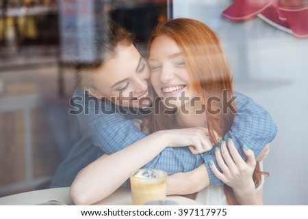 Two cute lovely happy young women hugging in cafe - stock photo