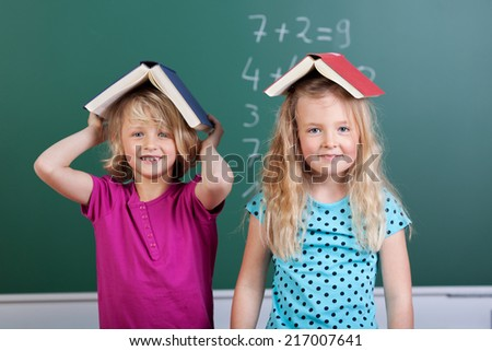 Two cute pretty little blond schoolgirls with book hats balancing open books on their heads and smiling playfully at the camera, blackboard background - stock photo