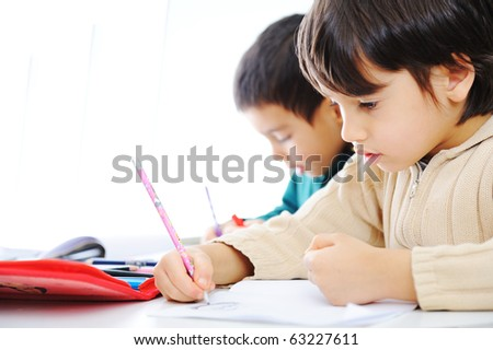Two cute school boys working on their homework together - stock photo