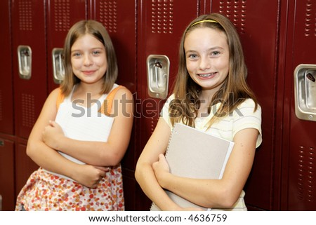 Two cute school girls leaning against their lockers. - stock photo