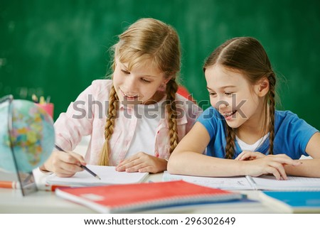 Two cute schoolgirls drawing together at lesson - stock photo