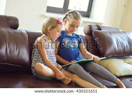 Two cute sister girls sitting at home and reading book together learning as a preschooler - stock photo