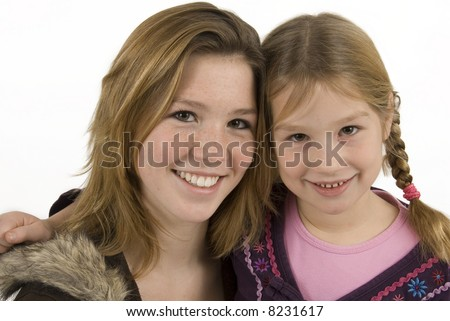 two cute sisters embracing against white background