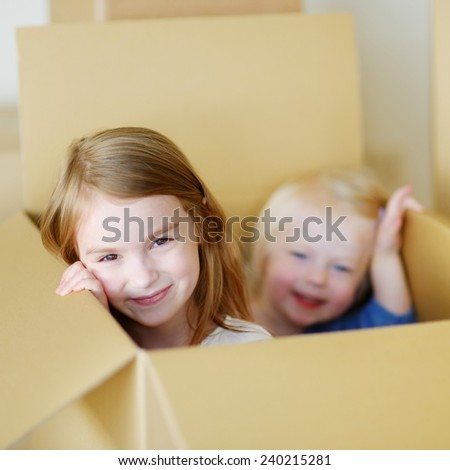 Two cute sisters girl having fun playing with a cardboxes while moving in her new home - stock photo