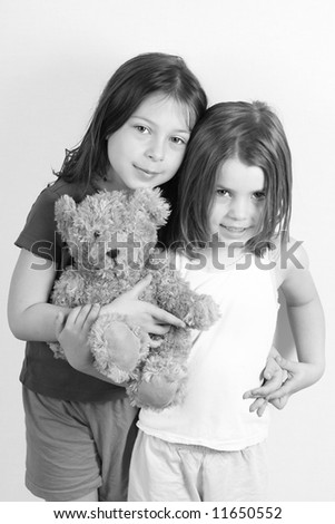Two Cute Sisters Holding A Teddybear and Holding Hands - stock photo
