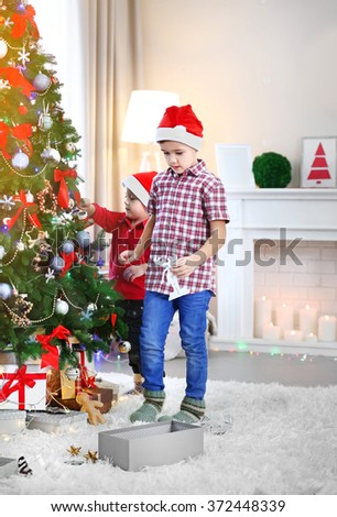 Two cute small brothers decorating Christmas tree - stock photo