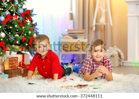 Two cute small brothers drawing on Christmas tree background - stock photo