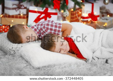 Two cute small brothers sleeping on carpet against Christmas tree - stock photo