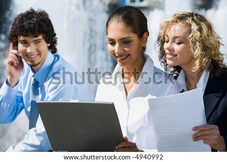 Two cute smiling female students are reading documents outside and handsome young man talking by the phone staring at them - stock photo