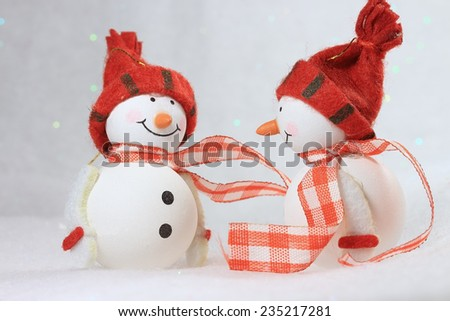 Two cute smiling snowmen.They are talking friendly. - stock photo