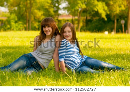 Two cute smiling teenage girls sitting on the grass on sunny spring day.