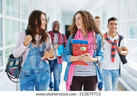Two cute students walking along college corridor and talking after classes - stock photo
