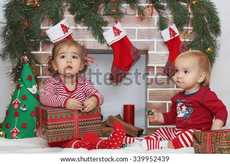 Two cute toddlers (boy and girl) sitting near Christmas decorated fireplace, winter holiday family concept