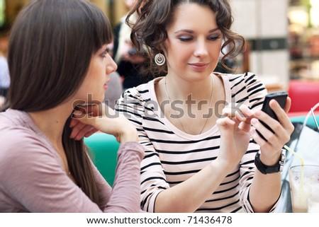 Two cute women having coffee break - stock photo