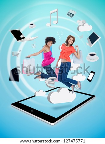 Two cute women jumping on a tablet pc against a digital blue background - stock photo