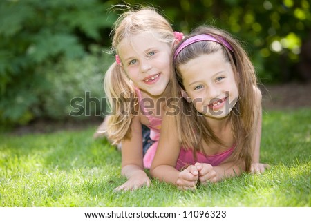 Two cute young girls lying together in the grass - stock photo