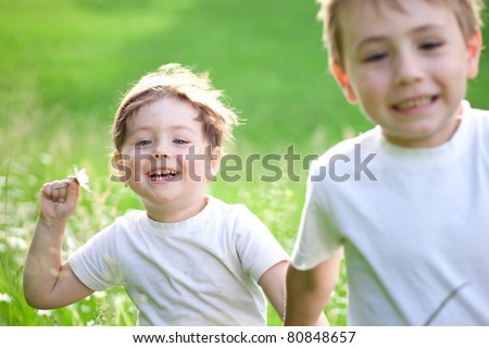 Two cute young preschool, child running and playing in green field.