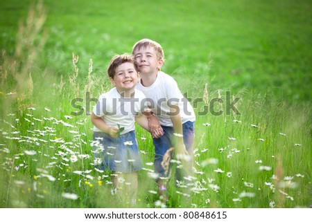 Two cute young preschool siblings playing in green field or meadow.