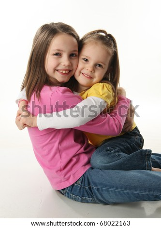 Two cute young sisters hugging each other, isolated on white - stock photo