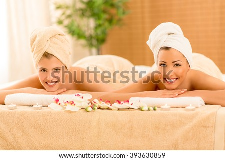 Two cute young women enjoying during a skin care treatment at a spa. Looking at camera. - stock photo